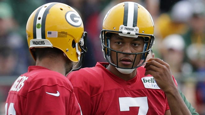 Packers quarterback Brett Hundley (right) talks with quarterback Aaron Rodgers.