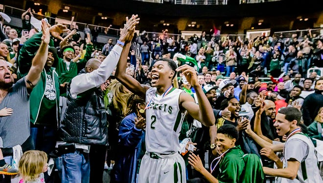 Eric Williams Jr. of New Haven high-fives a fan after the Rockets' defeated Ludington 45-36 to the school's first-ever Class B state championship on Saturday March 25, 2017 at the Breslin Center  in East Lansing, Michigan.