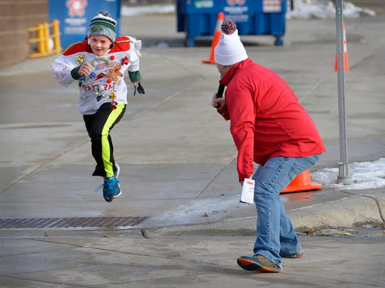 KCLD radio personality Derek Lee cheers on Sauk Rapids Squirts hockey team member Thomas Rosenkrans, 9, as he crosses the finish line in Saturday's Ugly Sweater-A-Thon 5K.
