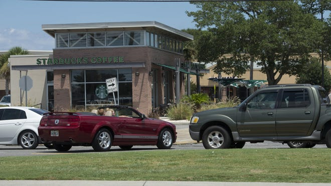 A car cuts across traffic to get to Starbuck in Gulf Breeze last year before the FDOT put up barriers to temporarily block the turning lane. The Florida Department of Transportation says it will be permanently closing the intersection, which has been the site of more than 100 accidents since 2008.
