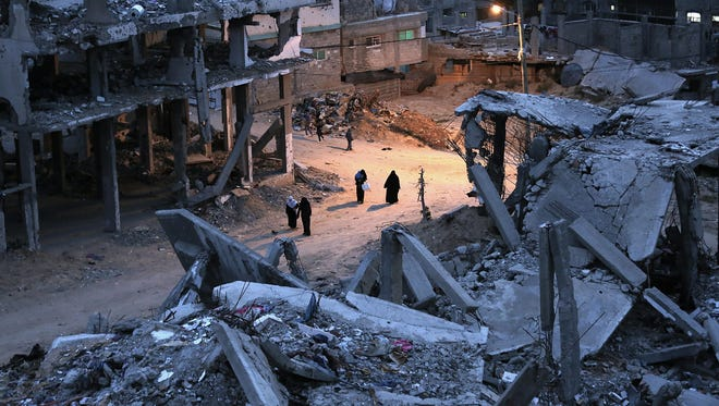 Palestinian women walk between houses that were destroyed during the 2014 Israel–Gaza conflict in the Al Shejaeiya neighborhood in east Gaza City on April 15, 2015.