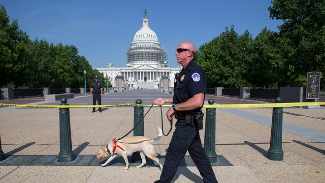 A Capitol Police officer walks with a search dog beside a police cordon outside the U.S. Capitol building while it is on lockdown on July 8, 2016.