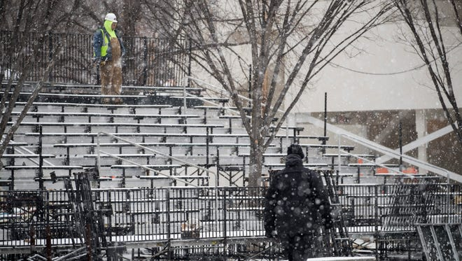 Workers build bleachers along the inaugural parade route in Washington.