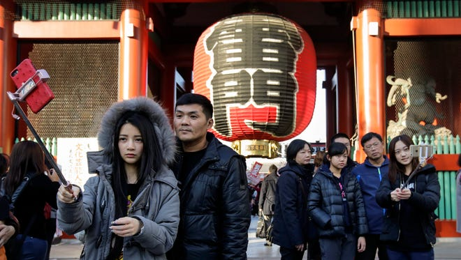 Tourists take selfies in front of a huge paper Lantern at Kaminarimon Gate of Sensoji temple in Tokyo on Jan. 30, 2017.
