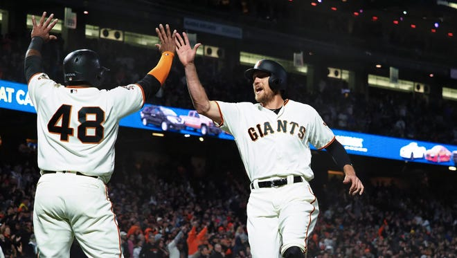 San Francisco Giants first baseman Pablo Sandoval (48) high fives left fielder Hunter Pence (8) after both scoring runs against the Arizona Diamondbacks during the fourth inning at AT&T Park.
