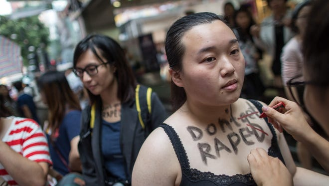 "A participant in the Hong Kong SlutWalk has the words ""Don't get raped"" written on her chest in Hong Kong. The participants took part in a rally condemning sexual, gender and body-based violence."