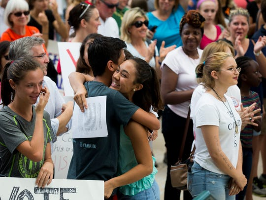 Kathryn Regala, 15, a freshman at Naples High School, right, gives classmate Chase Melton, 15, a hug after Melton gave a speech in front of the Collier County Courthouse to protest gun violence Friday, Feb. 23, 2018, in East Naples.