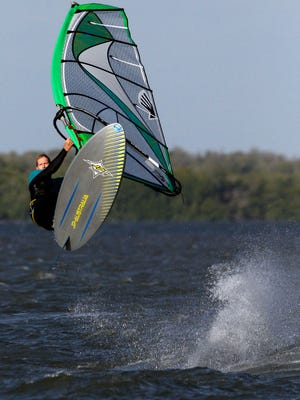 Windsurfer Roy Massey lets the wind carry him into the air in the waters off the Sanibel Causeway Monday.