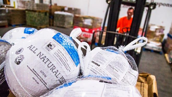 Tim Watson, a warehouse associate, uses a fork lift to move donated, frozen turkeys inside the United Food Bank, 245 S. Nina Drive, Mesa, Monday, November 23, 2015.
