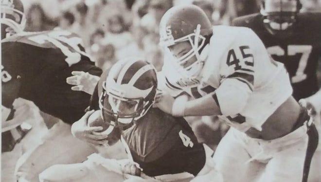 U-M quarterback Jim Harbaugh is sacked by #45 Joe Bergin in the first quarter of the MSU-U-M football game, October 1986.