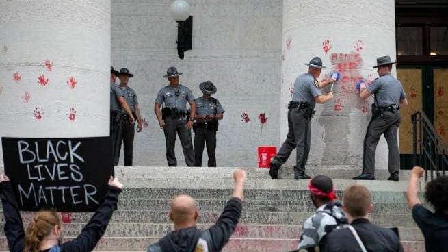 Protesters watch as State Highway Patrol troopers attempt to remove a handwritten message in red paint from a pillar of the Statehouse on Thursday. One protester said the paint was acrylic and could be washed off, but the troopers were having trouble removing the writing using brushes.