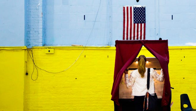 A woman enters a voting booth at a primary polling site in New Jersey is pictured June 7, 2016.