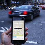 An Uber application is shown as cars drive by in Washington, D.C.