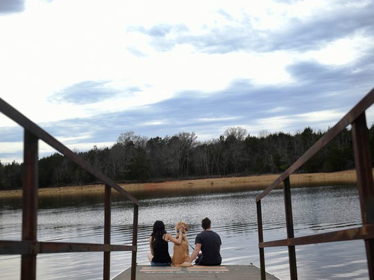 Carla and Mark Poiesz sit on the dock with their dog Dallas Winston recently at the Cook recreation area on J. Percy Priest Lake in Nashville.