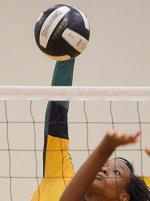 Carver's Demesha Bell (1) puts a shot over Lee's Virginia Hooks (17)during the Class 6A Area Volleyball Tournament at Carver High School in Montgomery, Ala. on Tuesday October 22, 2013.  (Mickey Welsh, Montgomery Advertiser