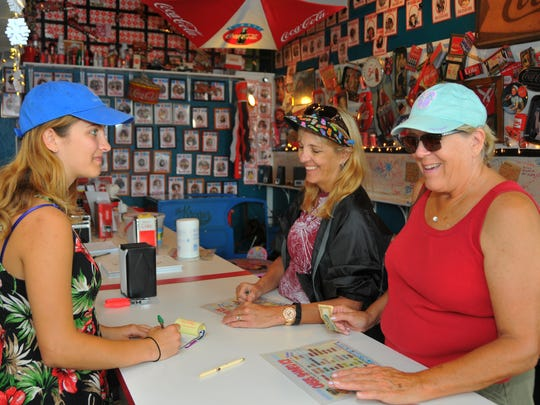 Cocoa Beach Jr./Sr. High School senior Hannah Stremmel takes an order from Peggy Arborgast and Shirley Gulden at Oasis Shaved Ice in downtown Cocoa Beach. Stremmel works after school and will work through the summer before going off to college.