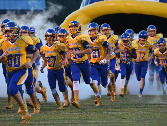 Wren High School players run on the field before kickoff