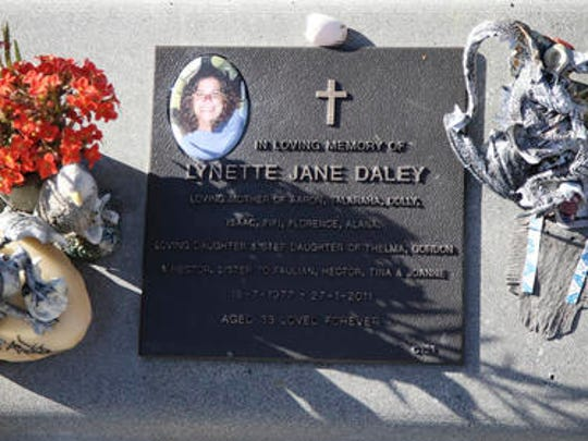 In this Aug. 16, 2016 photo, flowers and mementos adorn the grave of Lynette Daley, in Maclean, Australia. The brutal death of Daley, an Aboriginal woman, and the reluctance of officials to prosecute the white suspects, has highlighted a deadly racial divide in Australia, where Indigenous people remain the most disadvantaged segment of society.