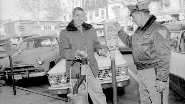 """Meter collector Sol Yacovelli and Patrolman Dino (Brownie) Barbetti """"bag"""" parking meters on Landis Avenue as a courtesy to Christmas shoppers during the 1963 holiday season."""