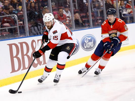 Ottawa Senators center Zack Smith (15) gets to the puck ahead of Florida Panthers defenseman Mark Pysyk (13) during the first period of an NHL hockey game, Tuesday, Jan. 31, 2017, in Sunrise, Fla. (AP Photo/Wilfredo Lee)