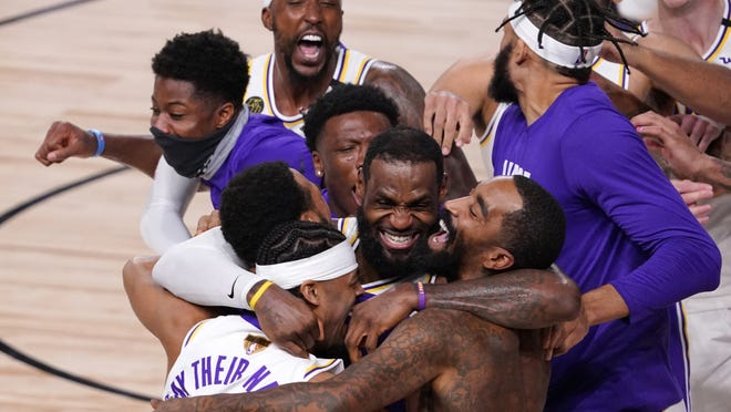 LeBron James (bottom center) celebrates with his teammates after the Los Angeles Lakers defeated the Miami Heat, 106-93, in Game 6 of the NBA Finals on Sunday in Lake Buena Vista, Fla.