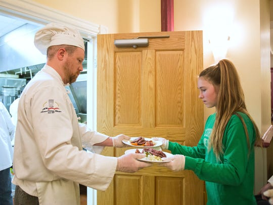 Kenneth Anderson hands a pair of plates over to Alyssa McCormick as she volunteers as a server at an International Night dinner in March.