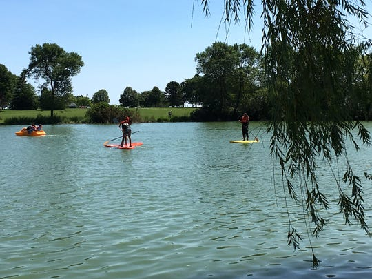 Paddle boarders splash in the algae-contaminated waters of the Juneau Park Lagoon on Tuesday. The lake remains open to boaters, though signs warning visitors of the algae dangers are planned, according to a spokesman for the Milwaukee County Parks system.