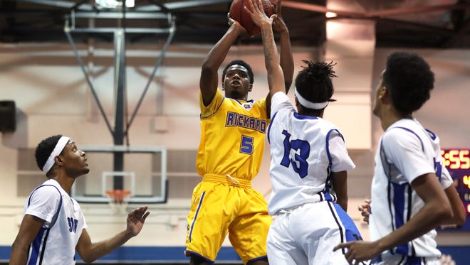 Rickards' Vincent McCray shoots over Godby's Kendric Sumlin during their game at Godby High School on Friday, Jan. 5, 2018.