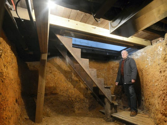 Chris Stock stands in the hiding room below a window that gives visitors a look into the basement of the William C. Goodridge Freedom House on East Philadelphia Street. The home is expected to open as an Underground Railroad museum next year.