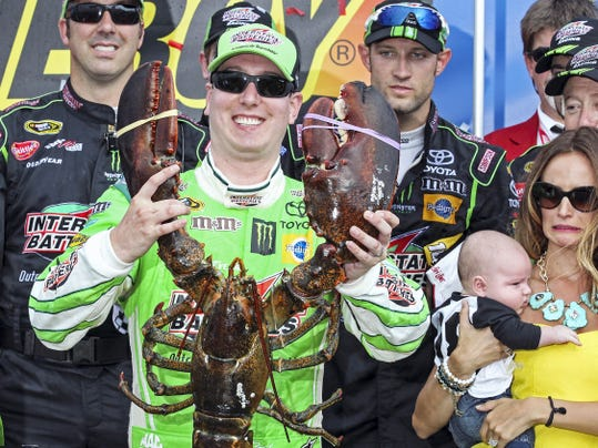 Kyle Busch holds the Loudon lobster trophy in victory lane, as his wife, Samantha, holding son Brexton, looks on at New Hampshire Motor Speedway on Sunday. After breaking his right leg and left foot in a crash the day before the season-opening Daytona 500, Busch missed the first 11 races of the season.