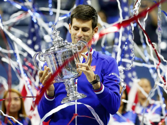 Novak Djokovic holds up the championship trophy after defeating Roger Federer during the men's championship match of the U.S. Open tournament Sunday in New York. Djokovic won, 6-4, 5-7, 6-4, 6-4.