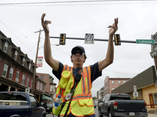 Justin Hinkle, a fire police officer with South Lebanon, directs traffic at Lehman and Ninth streets after a crane at CSR Recycling in the city of Lebanon hit a power line and knocked out power to a significant portion of the city on Friday, Aug.