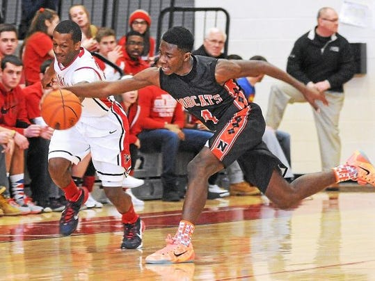 Plymouth Whitemarsh's Andre Mitchell and Northeastern's Kobi Nwandu reach for a loose ball during Saturday's PIAA Class AAAA first-round game. Plymouth Whitemarsh won, 71-46.