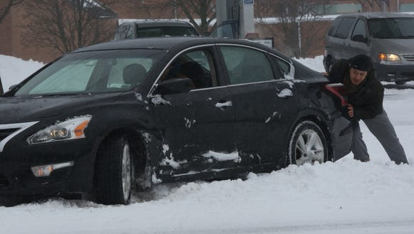 A man helps a car that is stuck in the snow on Route