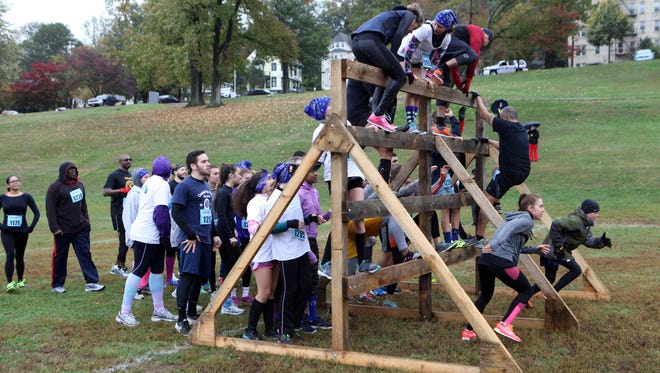 Competitors climb an obstacle as part of the event at the 5K mud run at Trevor Park in Yonkers, Oct. 22, 2016.