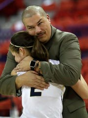 Appleton North coach Joe Russom hugs Kari Brekke after defeating Mukwonago to win the Division 1 state basketball championship.