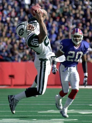Former Jets wide receiver Wayne Chrebet leaps to snare a pass as Buffalo Bills defensive back Henry Jones (20) pursues on Oct. 29, 2000, in Orchard Park.