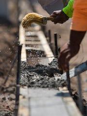 Construction workers pour concrete along a segment