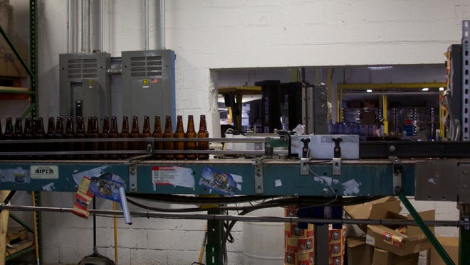 Empty bottles wait on a conveyor belt to be labeled, filled and packaged for sale at Full Tilt Brewing. Full Tilt's Bay IPA stickers hang off the machine's side.