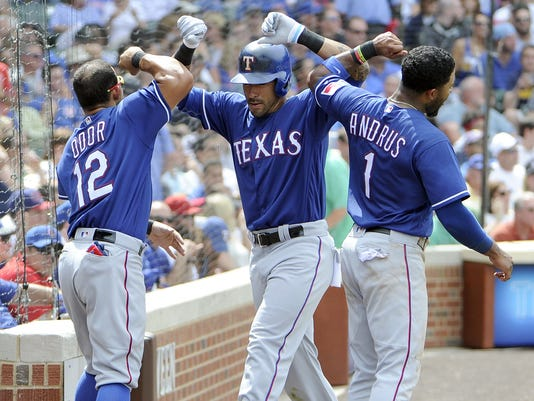 Texas Rangers' Ian Desmond, center, is greeted by his teammates Elvis Andrus (1) and Rougned Odor (12) after hitting a home run against the Chicago Cubs during the eighth inning of an interleague baseball game, Sunday, July 17, 2016, in Chicago. (AP Photo/David Banks)