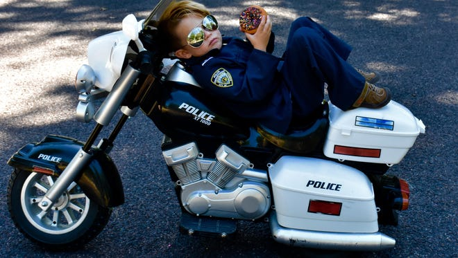 Officer Oliver relaxes on his bike and enjoys a doughnut while on break.