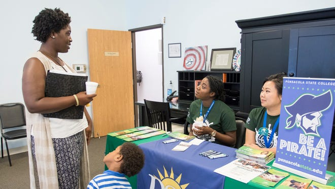 Jamahr Smith, 3, looks up at his mother Asia Williams as she talks with Pensacola State College representatives Vee Ho, right, and Rickell Irvin during The Escambia Project's One Stop Life Shop event at Pathways for Change Family Center in Pensacola on Friday, Sept. 15, 2017.