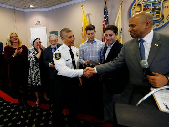 New Parsippany police chief Andrew Miller, surrounded by his family, is congratulated by Mayor Michael Soriano after his swearing in