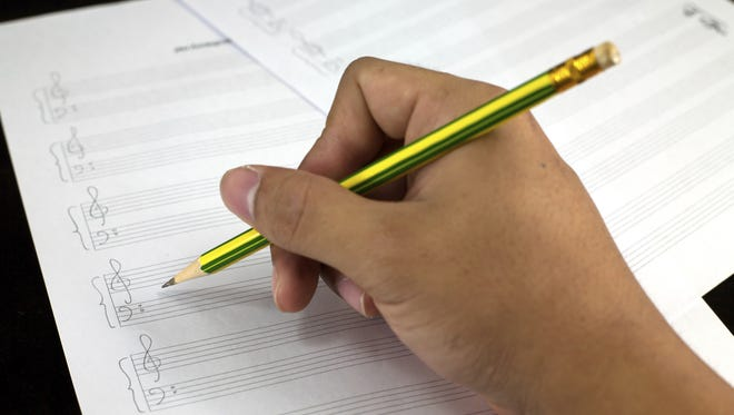 Stock photo: Composing musical notes on paper with pencil.