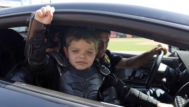 In this file photo from Tuesday, April 8, 2014, Miles Scott, dressed as Batkid, gestures as he sits in the Batmobile after throwing the ceremonial first pitch before a baseball game between the San Francisco Giants and the Arizona Diamondbacks in San Francisco.