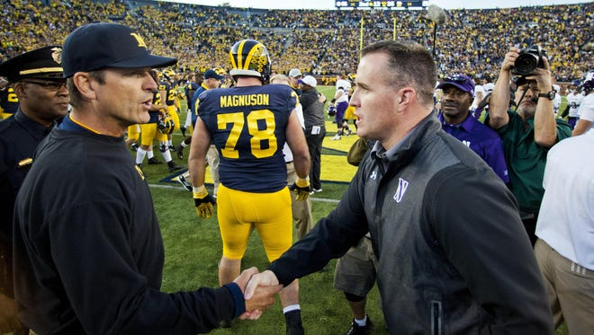 Michigan head coach Jim Harbaugh, front left, shakes hands with Northwestern head coach Pat Fitzgerald, front right, after an NCAA college football game in Ann Arbor, Mich., Saturday, Oct. 10, 2015. Michigan won 38-0. (AP Photo/Tony Ding)