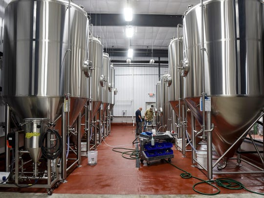 Brewers check on batches of beer May 24, 2017, at the