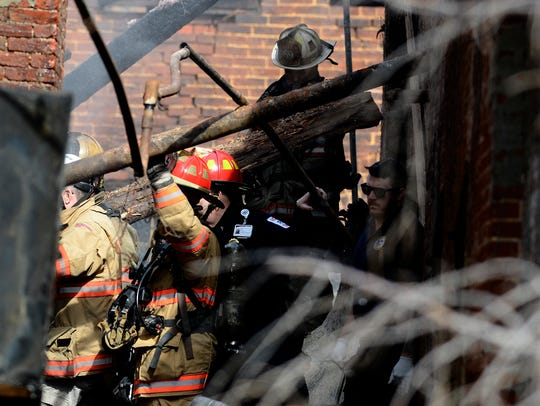 Firefighers work to rescue comrades trapped when a