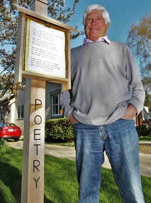 """Harvey """"Buzz"""" Wickman stands next to his poetry post outside his home in Shorewood on May 5, 2017.     ___________________________________________________________________________________________________________________________Summary: This gentleman has installed a poetry post in his front yard, and every few days he displays a different poem that he finds online. People walking by stop to read them and take photos."""