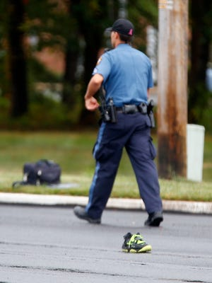 A Lakewood police officer walks past a shoe in the center of the roadway as the investigation of a fatal bicyclist struck accident on Route 70 eastbound at Buckingham Drive in the township continued Monday afternoon, October 9, 2017.
